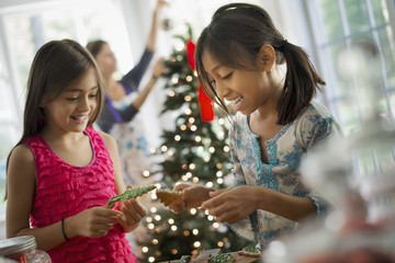 Two young girls decorating organic Christmas cookies.