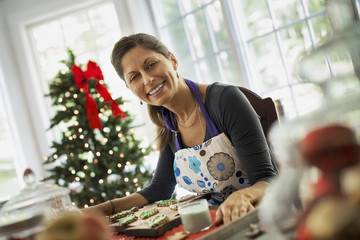 A woman working on organic homemade Christmas cookies, decorating and sprinkling decorations on green icing.