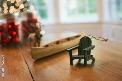 Christmas Decorations on a table. A handmade wooden canoe and a small chair.