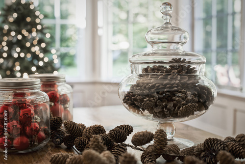 A decorative glass jar of pine cones and red glass baubles on a table top. Christmas decorations.