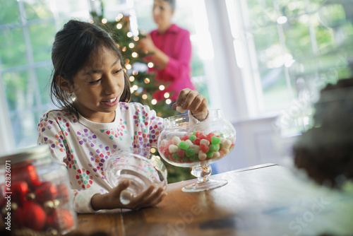 A young girl with a large glass jar of organic holiday gum drops.  Decorations for Christmas.