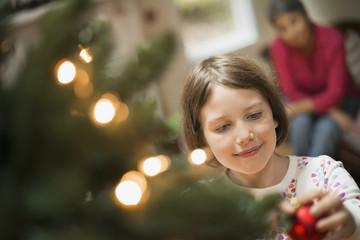 A girl placing a handmade ornament on a Christmas tree.