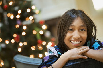 A young girl smiling and leaning over a chairback, in front of a Christmas tree.