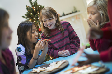 A group of children around a table, decorating organic Christmas cookies.