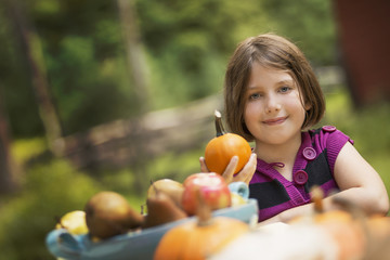 A young girl holding a pumpkin in her hand at a table outside. Harvest time.