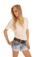woman light shirt denim shorts stand look down