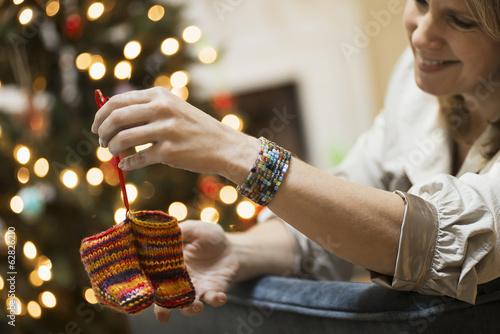 A young woman holding a pair of hand knitted baby booties.