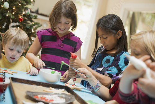 A group of children, girls and boys, around a table, decorating organic Christmas cookies.