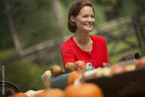 A woman in a red shirt, at a harvest table outdoors.