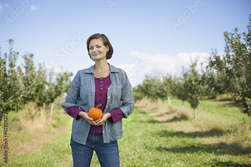 A woman in a plaid shirt holding an orange pumpkin or squash in her cupped hands, at an organic fruit farm.