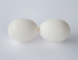 Two free range organic eggs with white shells, end to end, against a white background.