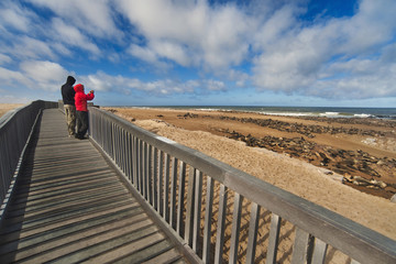 Tourists, two people on a beach walkway, Cape Cross, Namibia