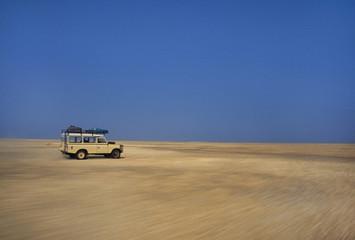 Vehicle moving across salt pans, Makgadikgadi Pans, Botswana