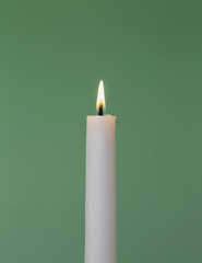 A thin white wax candle with a small  lit flame with a green background.