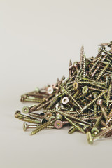 A pile of brass screws with a Philips crosshead.