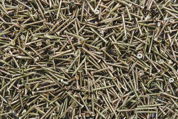 A pile of brass screws with a screw thread.