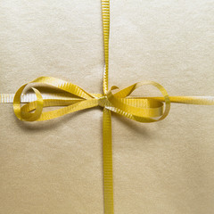 Close up of a tied bow and gold ribbon from a wrapped gift.