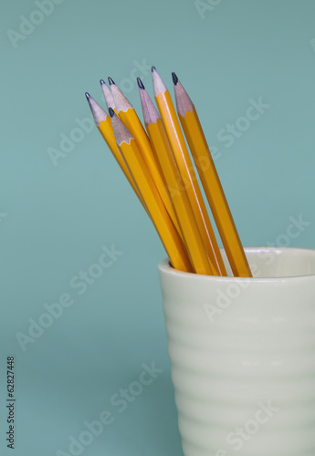 Sharpened pencils in cup, on a blue background.