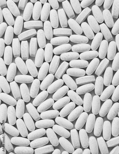 Vitamin C supplements, white oval tablets, taken for health reasons.