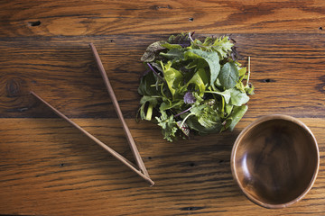 A small round polished wooden bowl and a clutch of organic mixed salad leaves, with wooden chopsticks.