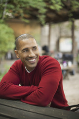 Scenes from urban life in New York City. A man in a red jumper seated at a bench, smiling.