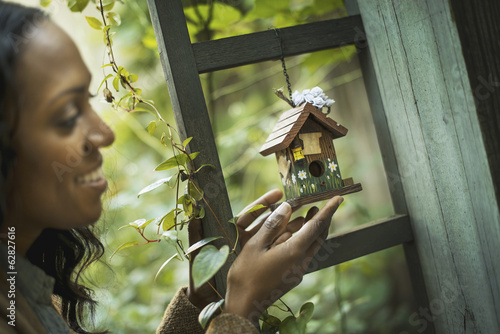 Scenes from urban life in New York City.  A woman holding a small painted bird house in an enclosure.