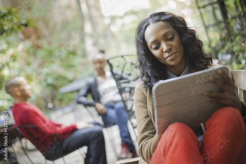 Scenes from urban life in New York City. Outdoors. Two people in background. A woman using a computer tablet or pad.