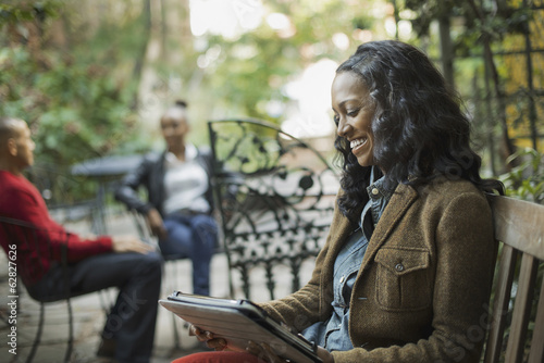 Scenes from urban life in New York City. A group of people sitting on a terrace outdoors. A woman using a computer tablet or pad.
