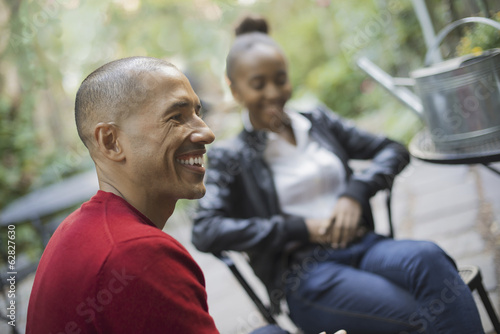 Scenes from urban life in New York City. A man and a teenage girl sitting outdoors. Laughing.