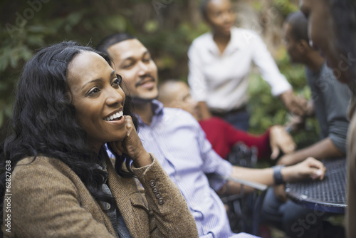Scenes from urban life in New York City. A group of friends sitting together in a leafy square. Men and women.