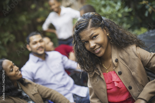 Scenes from urban life in New York City. A group of friends sitting together in a leafy square. Men and women. A teenage girl in the fore.