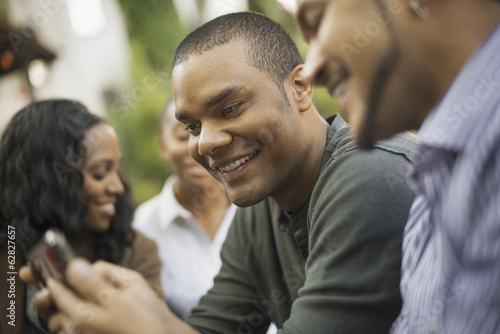 Scenes from urban life in New York City. Two men looking at a phone or handheld pad, smiling. Two women in the background.