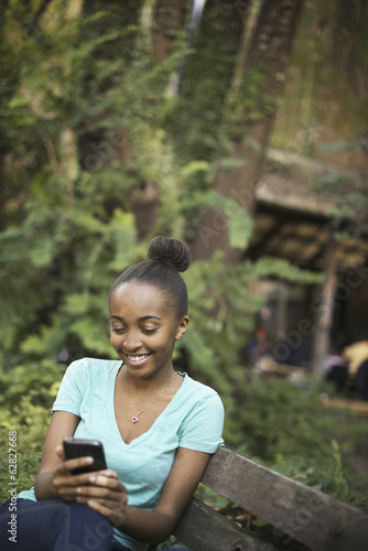 Scenes from urban life in New York City. A young teenage girl sitting on a bench, looking at a pad screen or texting.