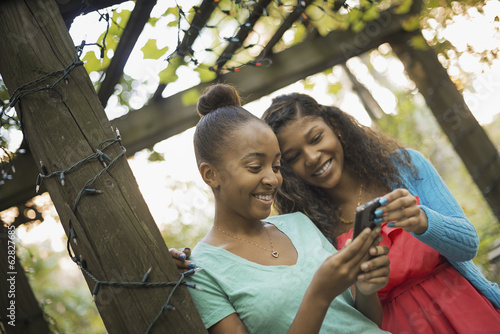 Scenes from urban life in New York City. Two girls looking at a cell phone or computer pad, laughing.