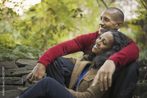 Scenes from urban life in New York City. A man and a woman, a couple sitting close together under the trees.