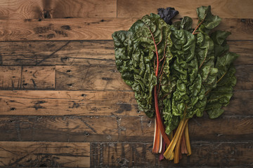 A group of red and orange chard leaves with bright coloured stems. Organic vegetables, frehsly picked, and placed on a wooden board.