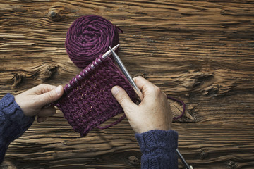 A woman holding two knitting needles, and a piece of knitting, in purple wool.