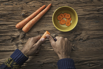 A person holding and slicing fresh carrots into a bowl.