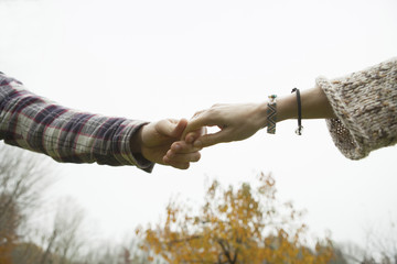 Two people holding hands, a couple outdoors.