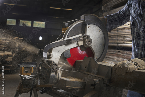 A reclaimed lumber workshop. A man in protective eye goggles using a circular saw to cut timber.