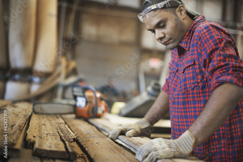 A reclaimed lumber workshop. A man measuring and checking planks of wood for re-use and recycling.