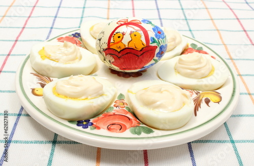 Halves of eggs with mayonnaise and painted egg on colorful plate