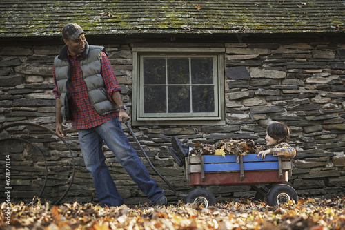A man in a padded jacket pulling a garden cart with a child sitting among the dried autumn leaves. A traditional stone building.