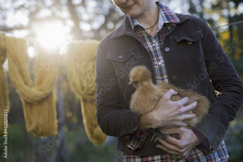 A woman holding a small brown fluffy chicken. A long brown knitted scarf on a washing line. Autumn sunshine filtering through trees.