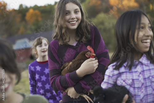 A group of four children in a group, two girls holding chickens, carrying them. A farmhouse and a hillside of trees with autumnal colours lit up by the sun.