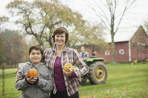 Two people, a woman and a child on an organic farm, carrying harvested vegetables, squashes and pumpkins.  Organic farming.