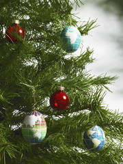 Still life. Green leaf foliage and decorations. A pine tree branch with green needles. Christmas decorations. A small group of red and blue tree ornaments. Oblong shapes with continents outlined on a blue background.