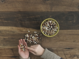 A person sorting different kinds of beans and pulses in her hands on a wooden table top.