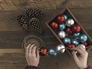 A woman threading Christmas shiny round ornaments on a piece of string. A small group of pine cones.