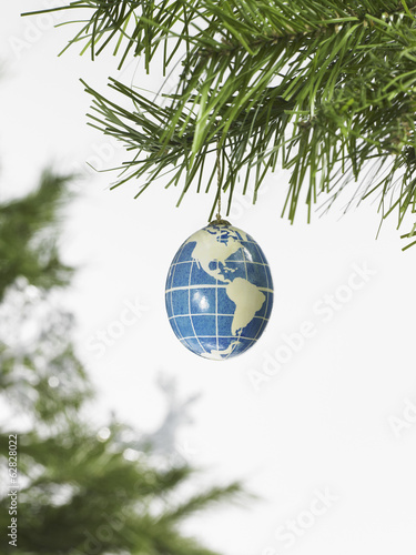 Still life. Green leaf foliage and decorations. A pine tree branch and a blue and white bauble. A globe with continents outlined on a blue background.